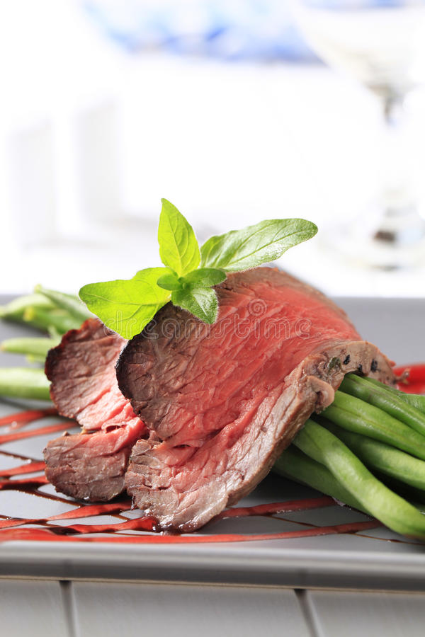 Beef steak and string beans. Slices of medium rare beef steak and string beans royalty free stock photography