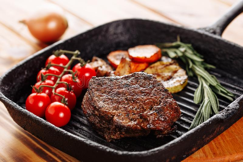 Beef Steak Tenderloin Rosemary Tomato on Grill Pan stock photography