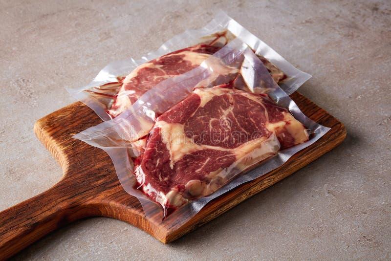 Beef steak vacuum sealed on stone table stock image
