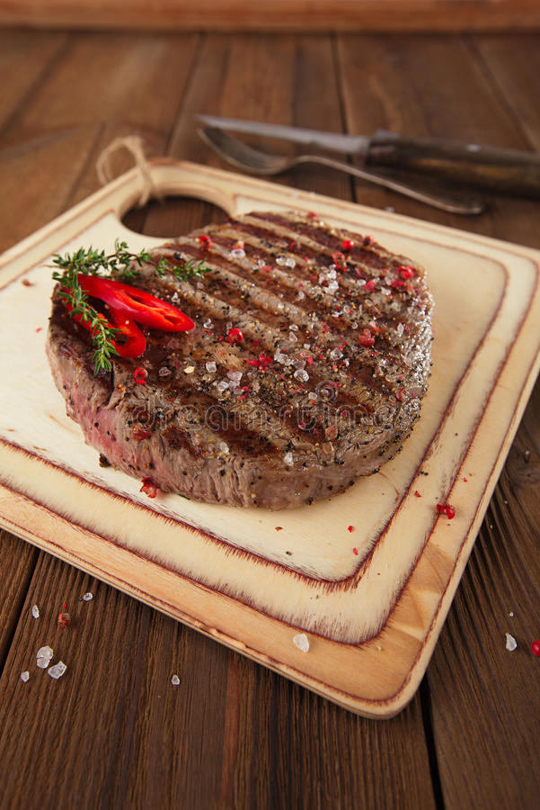 Download Beef Steak On A Wooden Board And Table Royalty Free Stock Photography - Image: 33648087
