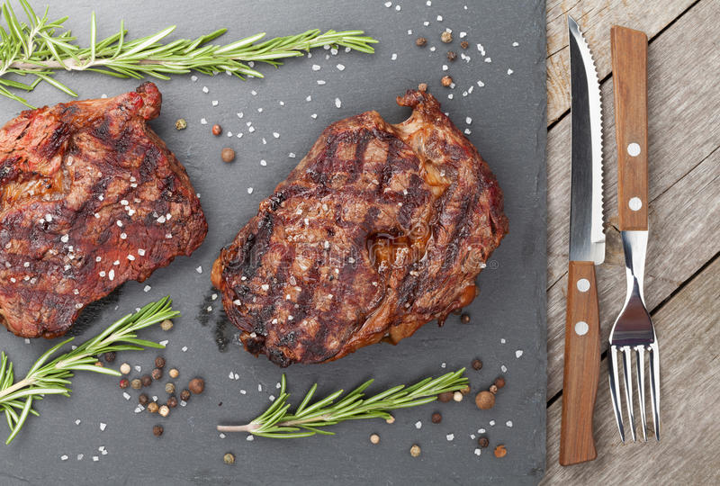 Beef steaks with rosemary and spices. On wooden table royalty free stock images