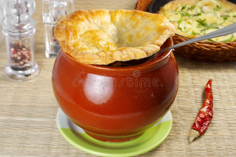 Beef stew in a crock pot. Covered with a circle of baked dough stock images