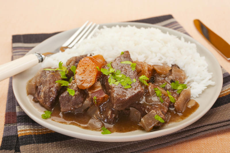 Beef Stew on a Plate with Rice. French beef stew in red wine, on a plate with rice. Known as daube de boeuf Provencal stock photo