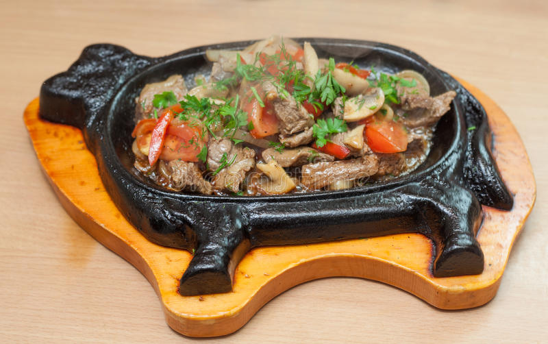 Beef stew with vegetables. Hot beef stew with vegetables on a cast iron bull form base stock photos