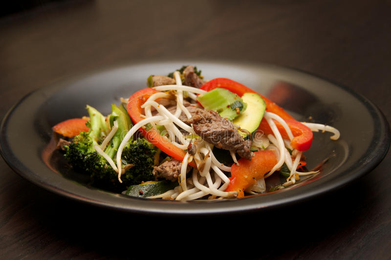 Beef Stir fry. On a black plate royalty free stock image