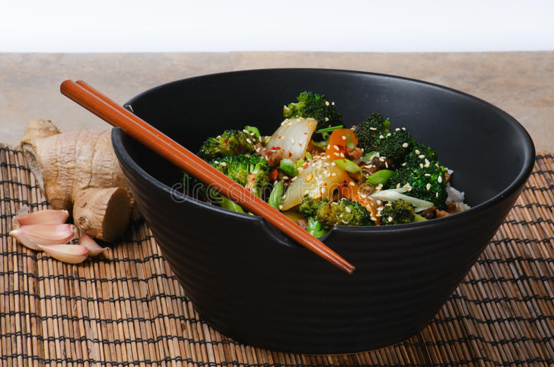 Beef Stir-Fry. With broccoli, carrots, onions, peppers, sesame seeds, and ginger on rice royalty free stock photos