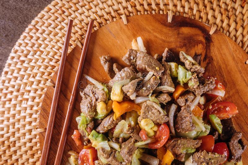 Beef stir-fry with bell peppers on wooden plate. Beef stir-fry with bell peppers, avocado on wooden plate, meal, lamb, lunch, dinner, dish, cuisine, hot, asia stock photo
