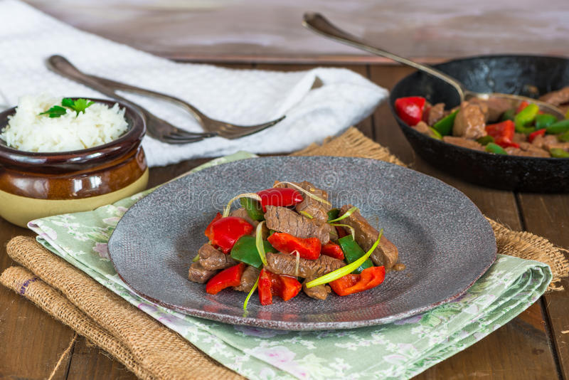 Beef stir fry. With peppers and oyster sauce on rustic wooden table royalty free stock photos
