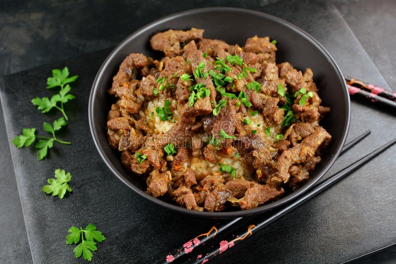 Beef Stir Fry with Rice. A set of photos showing a bowl of beef stir fry with cooked rice. Served in a bowl on black background stock photography