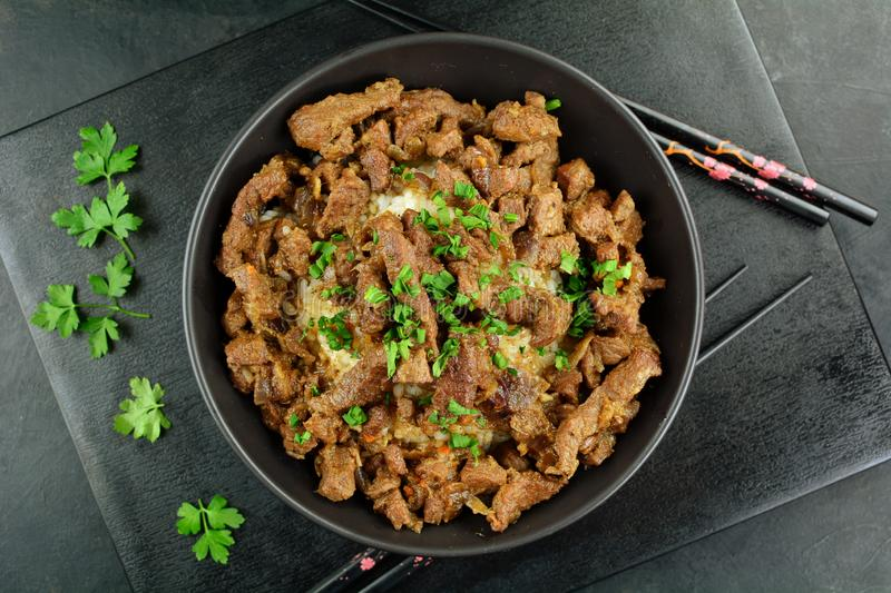 Beef Stir Fry with Rice. A set of photos showing a bowl of beef stir fry with cooked rice. Served in a bowl on black background royalty free stock photography