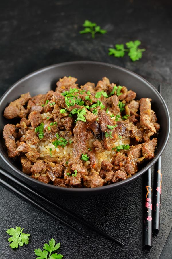 Beef Stir Fry with Rice. A set of photos showing a bowl of beef stir fry with cooked rice. Served in a bowl on black background stock image