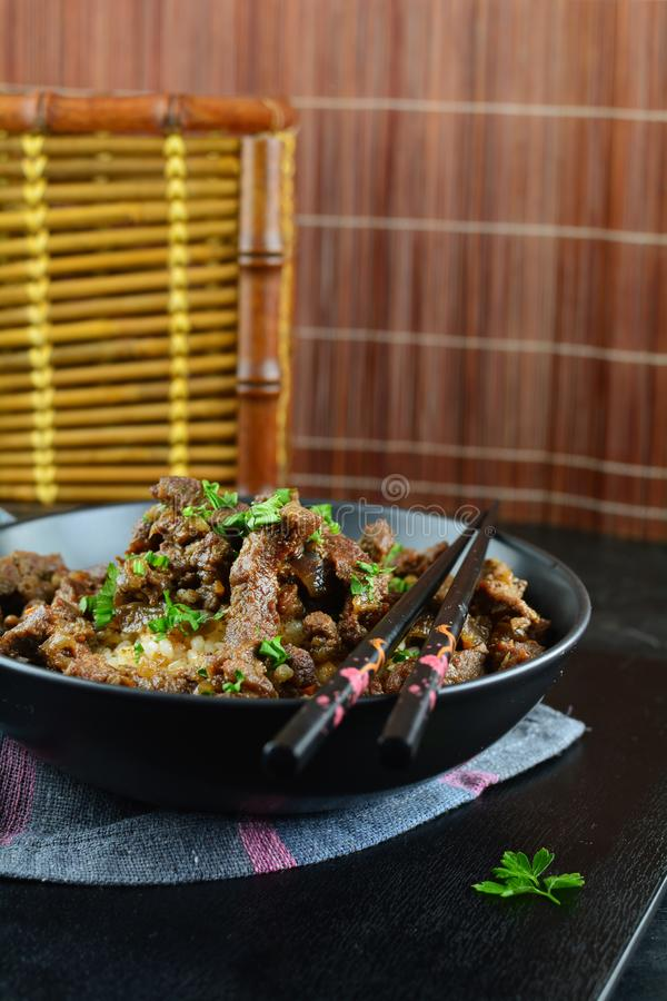Beef Stir Fry with Rice. A set of photos showing a bowl of beef stir fry with cooked rice. Served in a bowl on black background stock photo