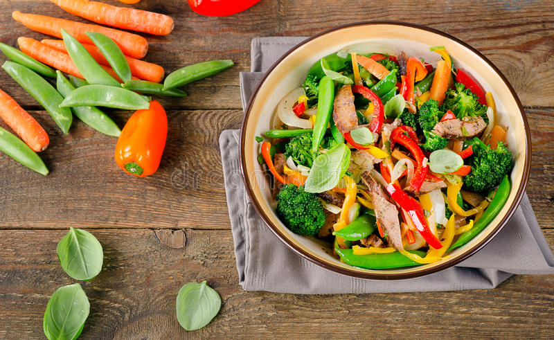 Beef stir fry with vegetables. On a rustic wooden table. Healthy eating. Top view stock photography
