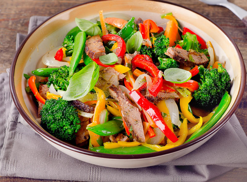 Beef stir fry with vegetables on wooden table. stock photography