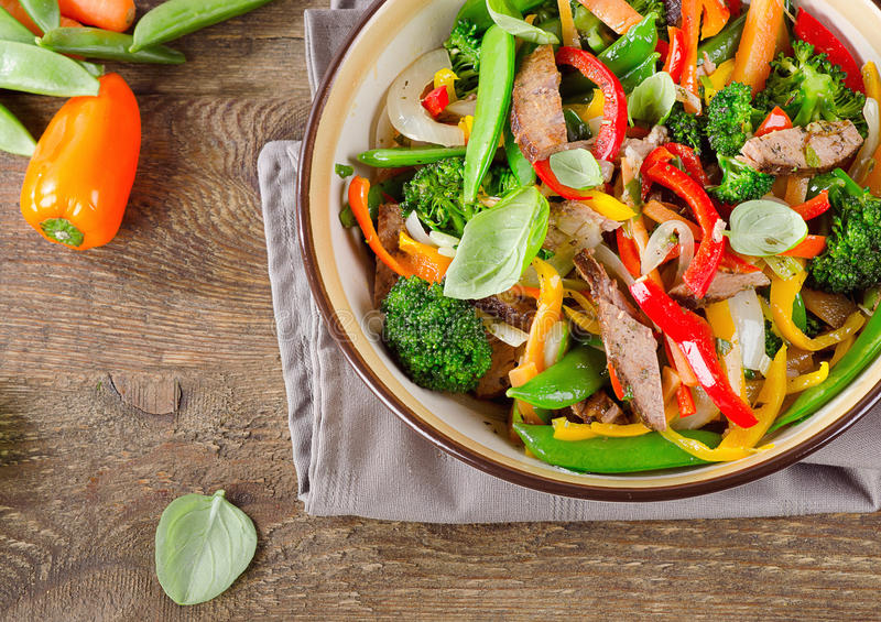 Beef stir fry with vegetables on a wooden table. Healthy eating. Top view royalty free stock image