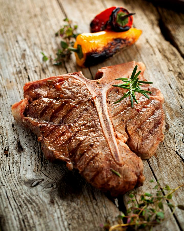 Beef T-bone steaks on dark old wooden board stock image