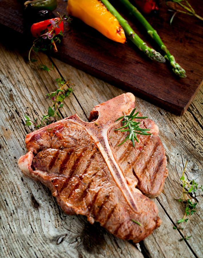 Beef T-bone steaks on dark old wooden board royalty free stock images