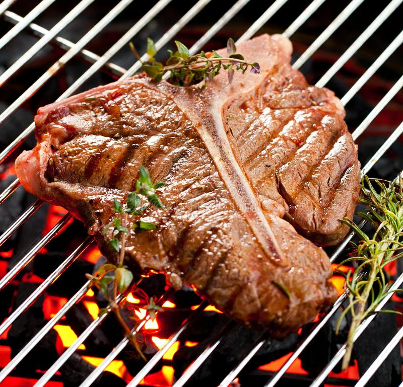 Beef T-bone steaks on the grill with flames. stock image