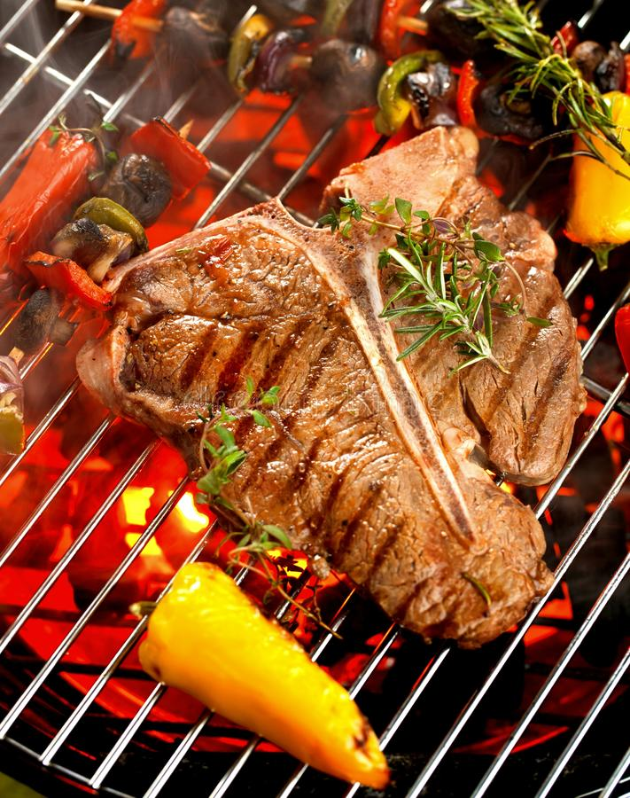 Beef T-bone steaks on the grill with flames. stock photography