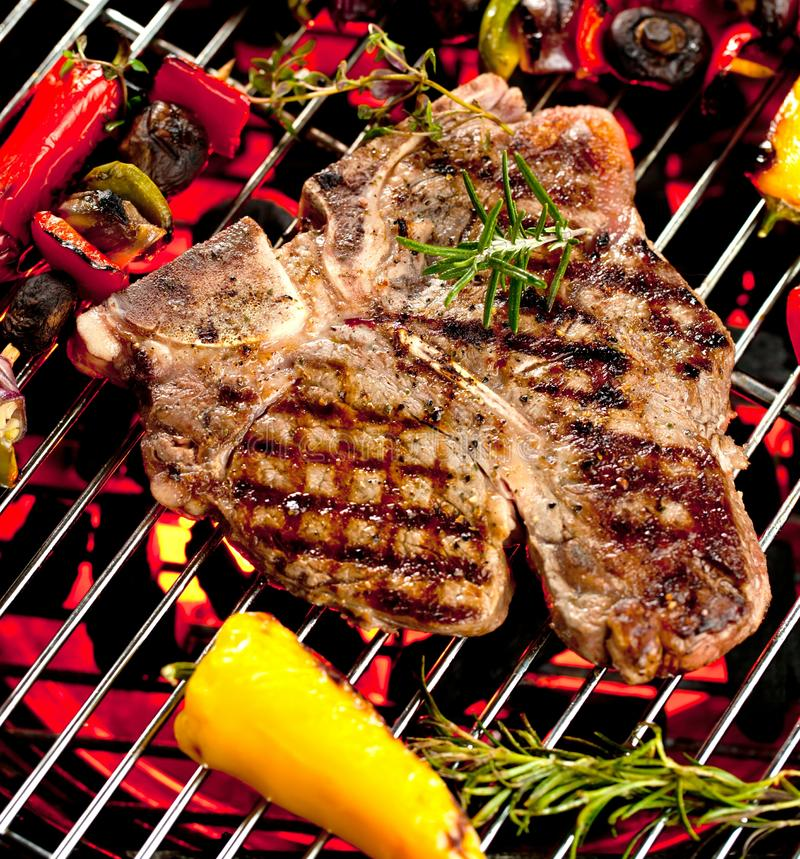 Beef T-bone steaks on the grill with flames. royalty free stock photo