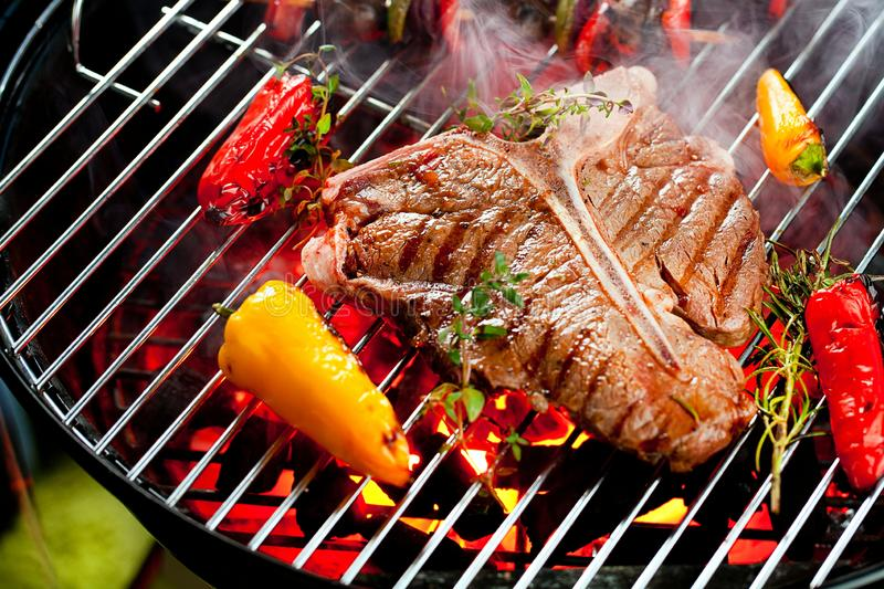 Beef T-bone steaks on the grill with flames. royalty free stock photography
