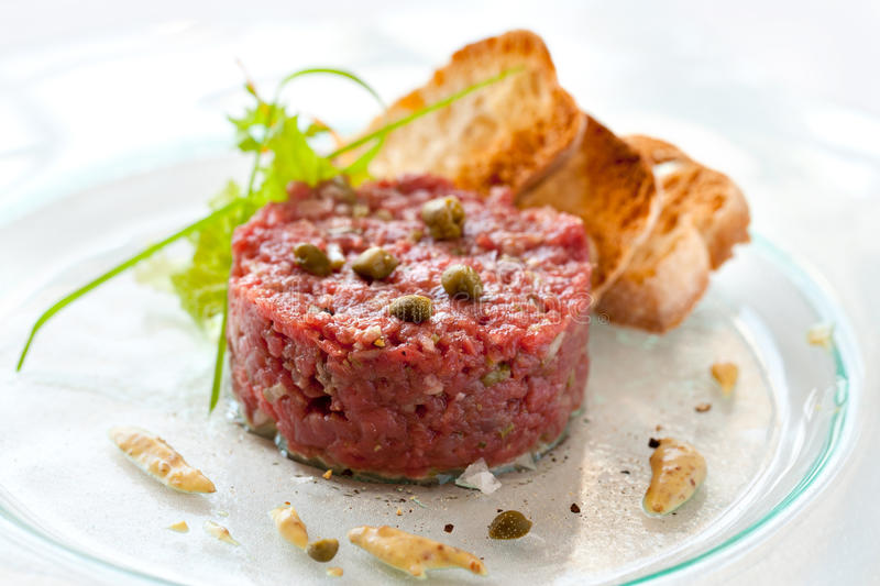 Beef tartar with capers. Close up of beef tartar with capers and small toasts stock photography