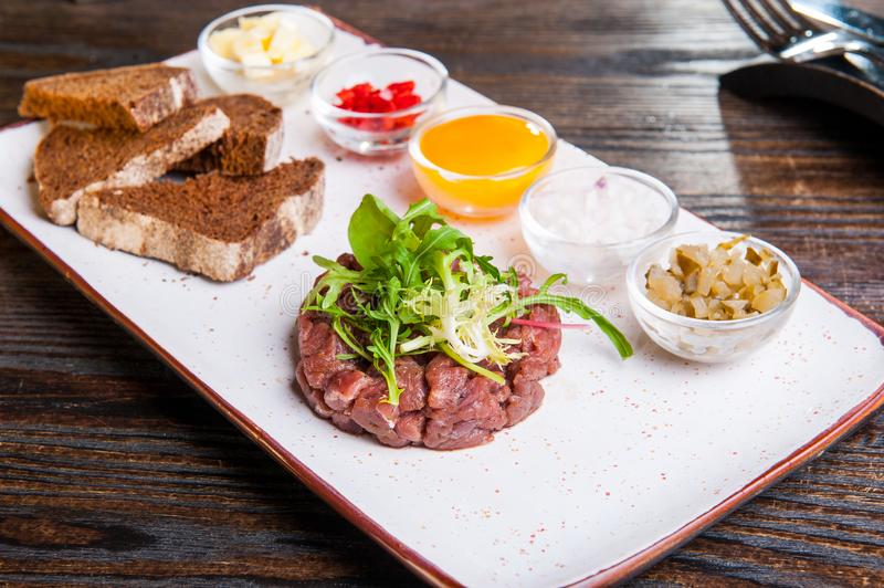 Beef tartare with arugula salad, crisp bread chips, sauces and snacks on white plate on the served restaurant table royalty free stock photos