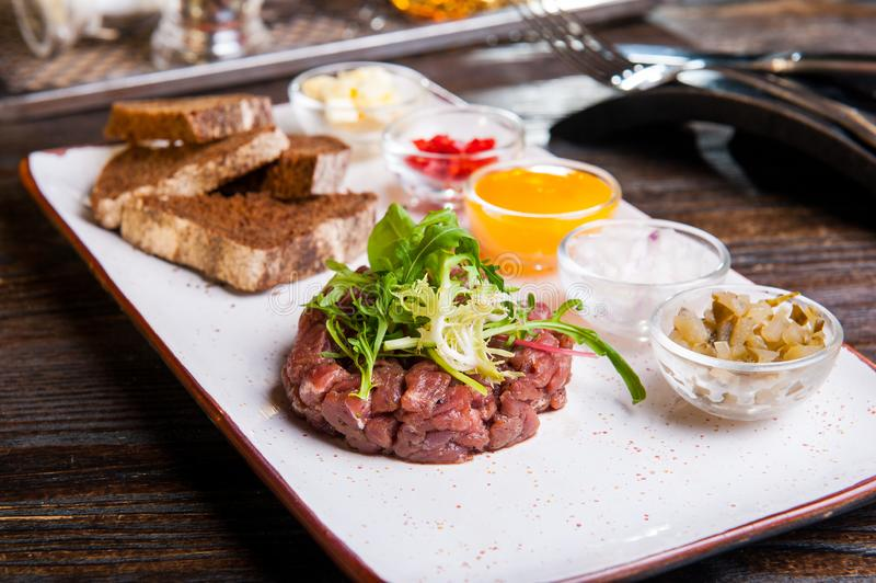 Beef tartare with arugula salad, crisp bread chips, sauces and snacks on white plate on the served restaurant table stock images