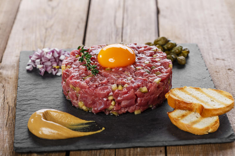 Beef tartare with capers yolk. And mustard stock photos