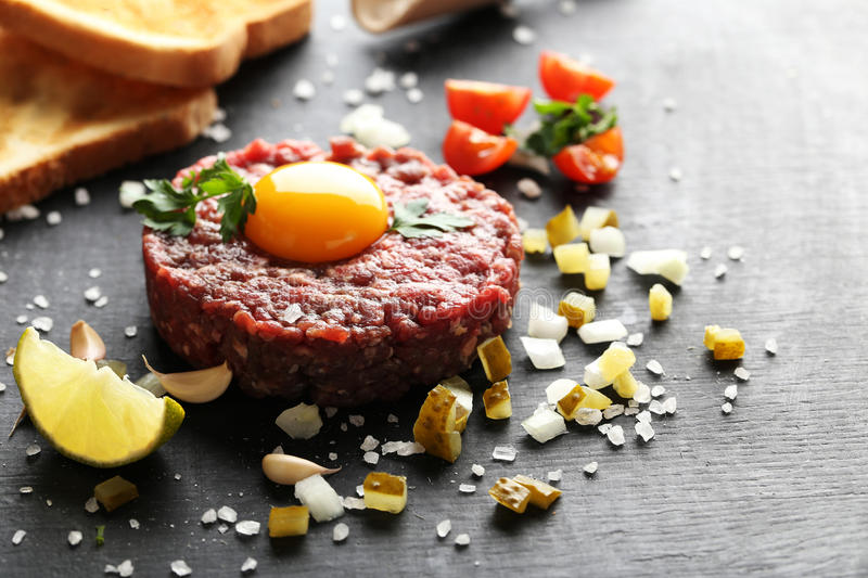 Beef tartare with egg yolk. On a black wooden table royalty free stock photos