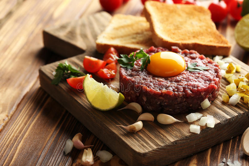 Beef tartare with egg yolk. On a brown wooden table stock images