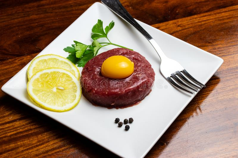Beef tartare with egg yolk on a wooden table and white plate stock photography