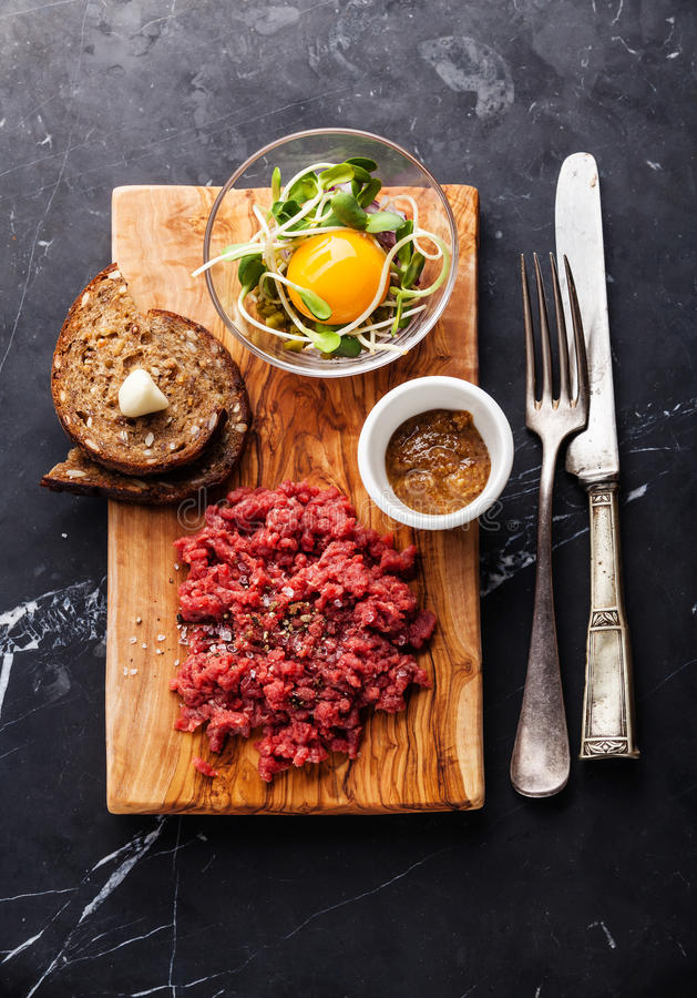 Beef tartare steak and garlic toasts. Beef tartare steak with salad and garlic toasts on dark marble background royalty free stock images