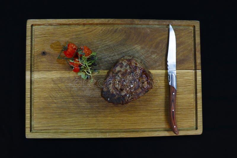 Beef tenderloin steak in a wooden board royalty free stock images