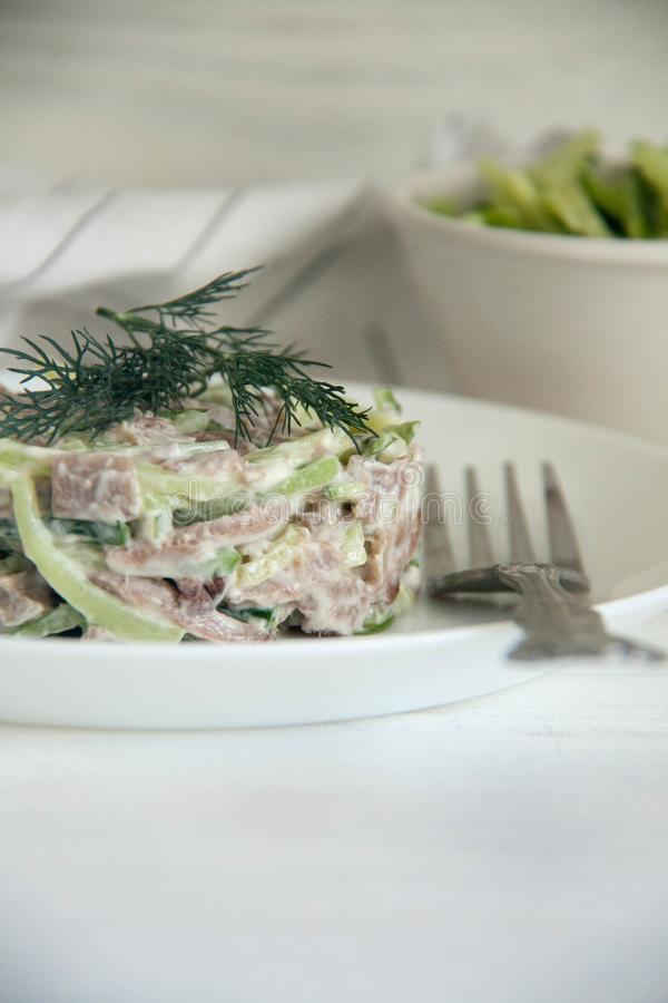 Beef tongue and fresh cucumber salad. Perfect cozy and delicious lunch: beef tongue and fresh cucumber salad with mayo and horseradish on a white plate stock photos