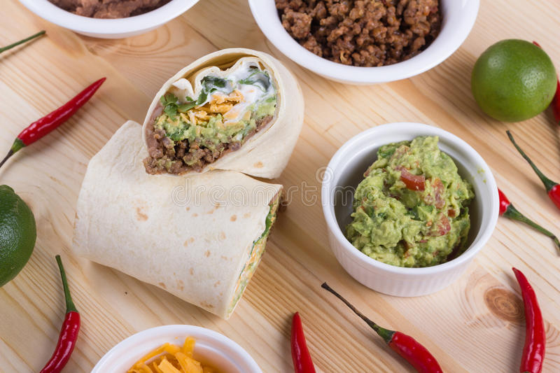 Beef tortilla. Beff tortilla with grated cheddar, guacamole, fried beans and chili royalty free stock image
