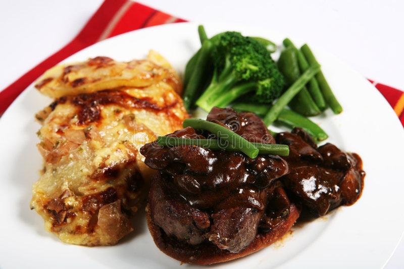 Beef tournedos dinner. A meal of beef tournedos on a crouton, topped with mushrooms in a brown sauce and served with beans, peas and onion and potato gratin stock images