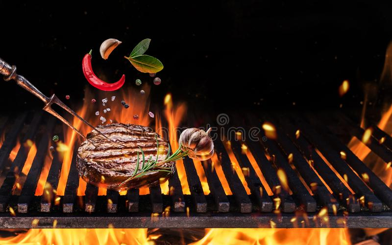 Beefsteak with spices fly over the flaming grill barbecue fire stock image