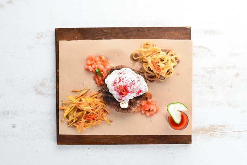 beefsteak Ternera con el huevo escalfado y el jugo de tomate En un fondo de madera foto de archivo