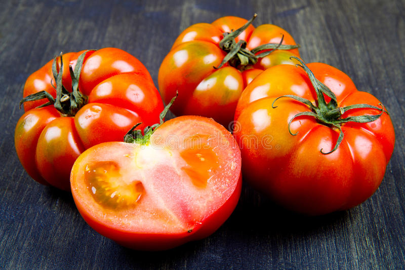 Beefsteak tomatoes. Isolated on wood stock photography