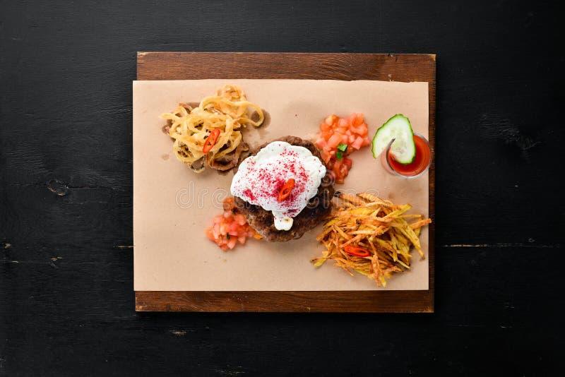 beefsteak Vitello con il succo di pomodoro e dell'uovo affogato Su una priorit? bassa di legno fotografia stock libera da diritti