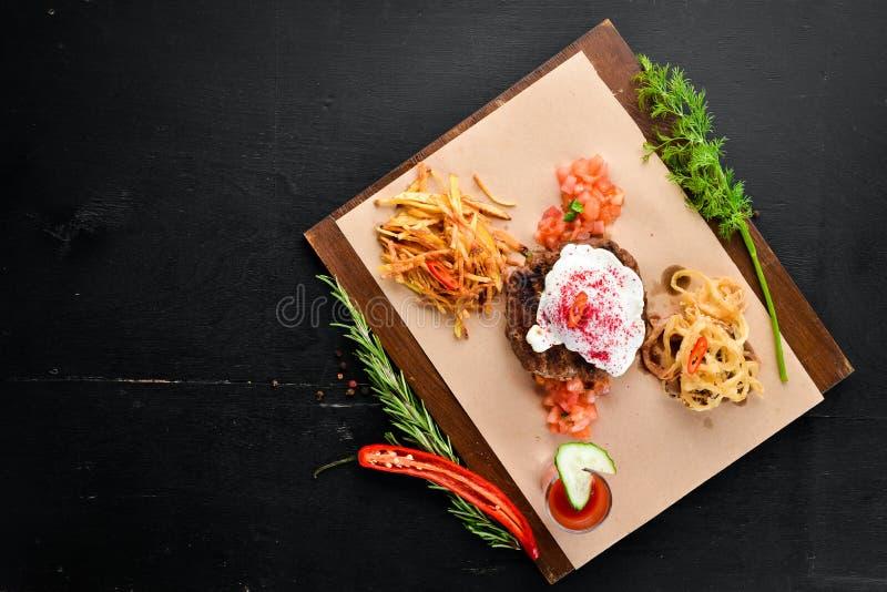 beefsteak Vitello con il succo di pomodoro e dell'uovo affogato Su una priorit? bassa di legno immagini stock