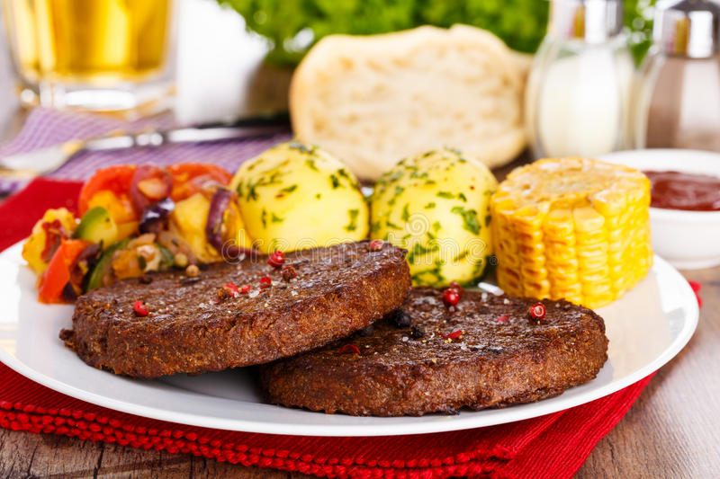 Beefsteaks with grilled veggies. 2 pieces of beefsteaks with fresh sliced corncob, potatoes and grilled veggies royalty free stock image