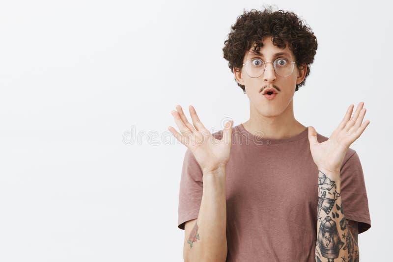 Beeindruckt mit neuer stilvoller Modelinie Surprised begeisterte attraktiven jungen europäischen Kerl mit dem gelockten dunklen H stockbilder