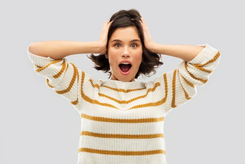 Beeindruckte Frau im Pullover, der zu ihrem Kopf hält lizenzfreie stockfotos