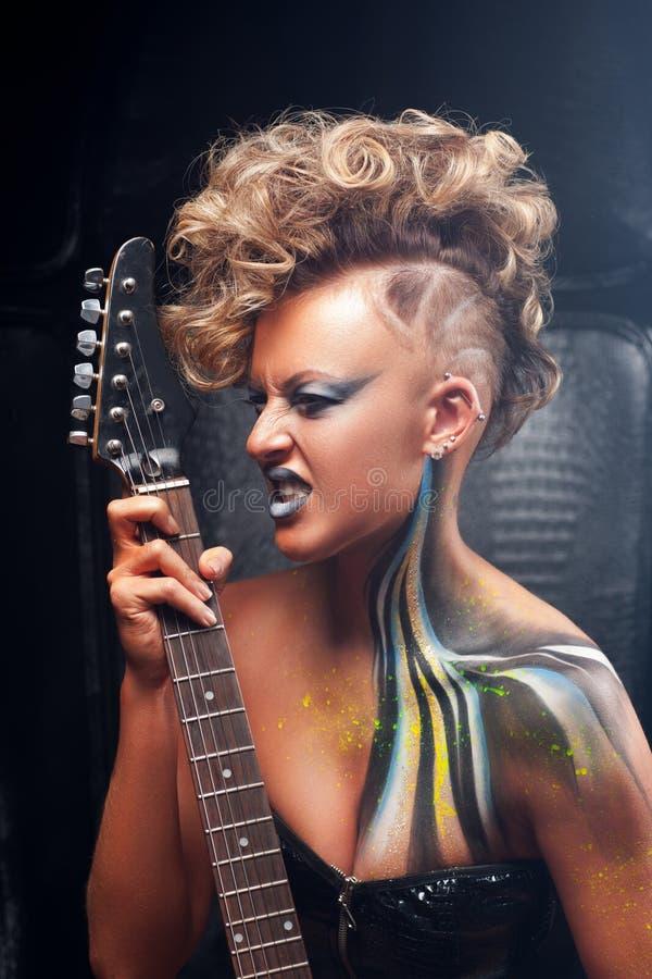 Beeindruckter Punkmusiker, der auf Gitarre spielt stockfotos
