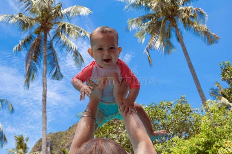 beeindrucktes kleines Kind des Babys hob hoch in Arme gegen den Himmel und tropischen die Palmen an Kind gekleidet in einem koral lizenzfreies stockfoto