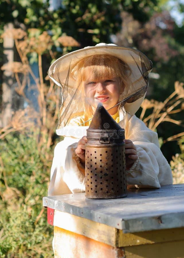 Beekeeper маленькой девочки дует курильщик для пчел стоковая фотография