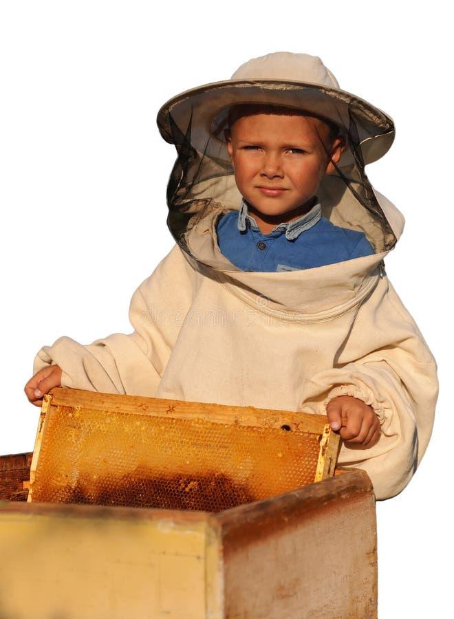 Beekeeper молодой мальчик который работает в пасеке стоковое изображение
