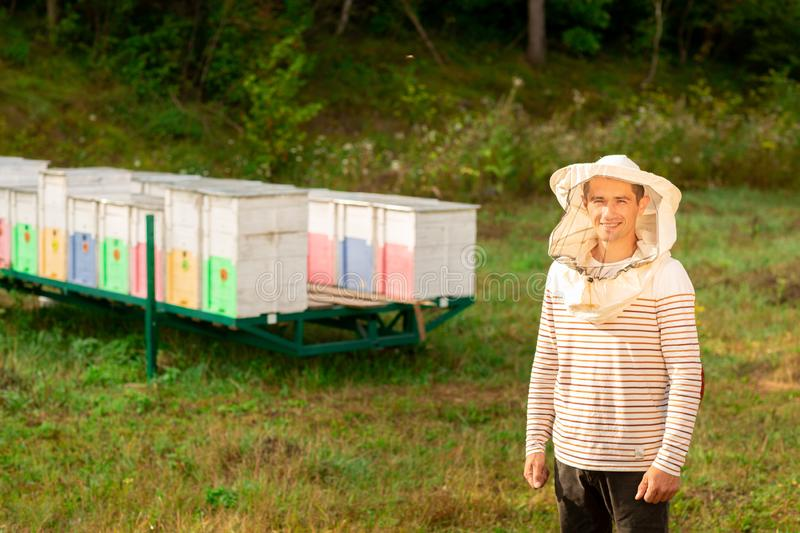 Beekeeper in a protective cap poses against the background of colored beehives in nature stock images